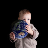 Boy holding his future world. Toddler holding globe isolated on black. Environmental concept Royalty Free Stock Photo
