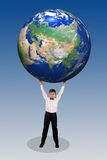 Boy holding in his hands over his head a large globe Stock Photography