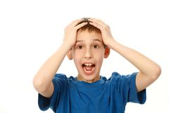 Boy holding his head in shock. Portrait of surprised boy isolated on white Stock Photos