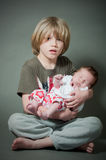 Boy holding his new born baby sister Stock Image