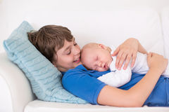 Boy holding his newborn baby brother Royalty Free Stock Image