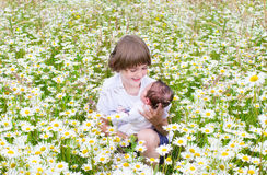 Boy holding his newborn baby sister in flowers Stock Images