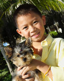 Boy holding his puppy Royalty Free Stock Image