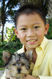 Boy holding his puppy stock photo