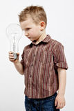 Boy holding huge bulb Royalty Free Stock Photos