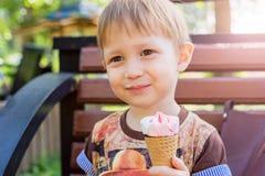 Boy holding an ice cream cone. A boy holding an ice cream cone. Boy sitting on a bench in the park and eat ice cream. Sunny summer day Stock Photos