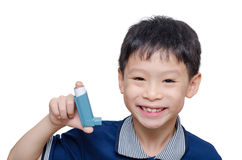 Boy holding inhaler and smiles. Young Asian boy holding inhaler and smiles over white royalty free stock images