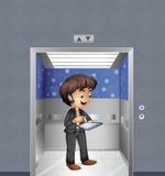 A boy holding an ipad inside the elevator Stock Photos