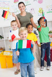 Boy holding italian flag. A cute young boy holding italian flag in classroom with classmates and teacher with diverse flags in background royalty free stock photography