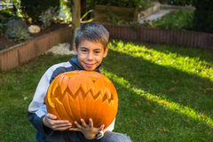Boy holding jack-o-lantern from big pumpkin. Child,boy sits on the ground with a jack-o-lantern, selfmade from a big pumpkin Royalty Free Stock Photos