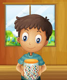 A boy holding a jar of candy balls Royalty Free Stock Image