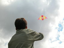 Boy holding a kite soaring, goal dream sky. Boy holding a high flying paper kite Stock Photos