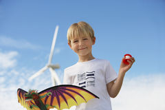 Boy Holding Kite At Wind Farm Stock Images