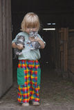 Boy holding kittens. Blond boy holding two kittens at the stable door Royalty Free Stock Photos