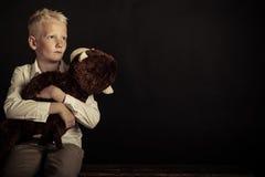 Boy holding large plush toy over black background Stock Image