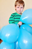 Boy holding a lot of balloons Stock Photos
