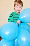 Boy holding a lot of balloons stock photos