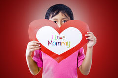 Boy give love card to mom. Boy is holding a love card for his mommy Royalty Free Stock Image