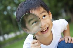 Boy holding magnifier Stock Image