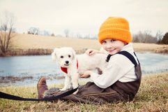 Boy holding Maltese dog by pond in country. Young boy wearing overalls and hat holds his pet Maltese doggie on his lap Stock Photography
