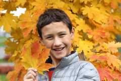 Boy holding maple leaf in falling Royalty Free Stock Photography