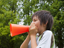 Boy holding megaphone. Asian boy cheering with megaphone Royalty Free Stock Images