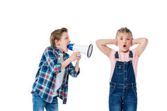Boy holding megaphone and screaming at littke girl closing ears Royalty Free Stock Photos