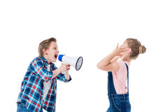 Boy holding megaphone and screaming at littke girl closing ears Royalty Free Stock Images