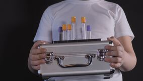 Boy is holding a metal suitcase. Medical case contains test tubes with samples for coronavirus. Boy is careful of the