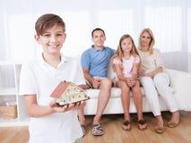 Boy Holding Miniature Model Of House Stock Image