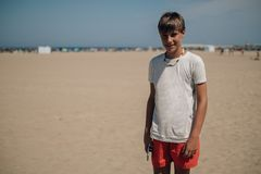Free Boy Holding Mobile Phone On The Sunny Beach And Smiling Royalty Free Stock Photography - 127037717