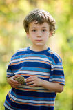 Boy holding a mushroom. Young boy outdoors in summer holding a wild edible mushroom (morel) he picked from the forest Royalty Free Stock Photos