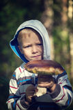 Boy holding mushroom in a forest Royalty Free Stock Photography