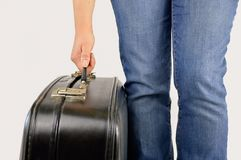 Boy holding an old suitcase. Close up hand of a man picking up an old black suitcase with a white background Stock Photos