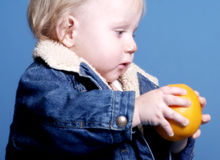 Boy holding orange. A little baby boy holding an orange royalty free stock images