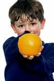 Boy holding orange. Young boy holding an orange Royalty Free Stock Photo