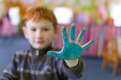 Boy holding out painted hand. Preschool boy holding out blue painted hand Royalty Free Stock Photography
