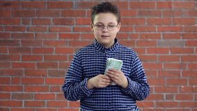 A boy with a wad of money in his hands stock footage