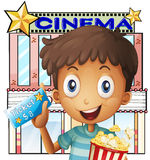 A boy holding a pail of popcorn and a ticket outside the cinema Stock Images