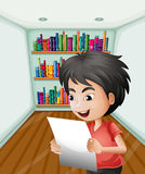 A boy holding a paper inside the room Royalty Free Stock Images