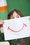 Boy Holding Paper With Smile Drawn On It Stock Image