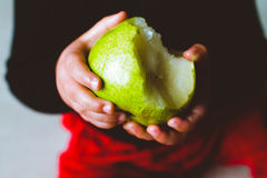 Boy holding a pear Royalty Free Stock Images