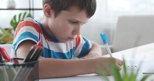 Boy writing in book at home. Boy holding pen and writing in his notebook stock video