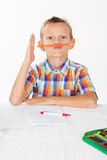Boy is holding pencil between nose and mouth Stock Images