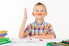Boy is holding pencil between nose and mouth Royalty Free Stock Photo