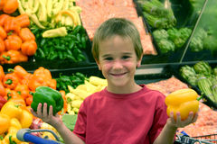 Boy Holding Peppers. Boy in produce holding peppers at the grocery store Stock Photos