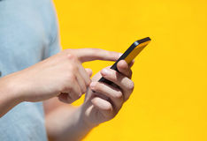 Boy holding a phone and a touch screen against a yellow wall Stock Images