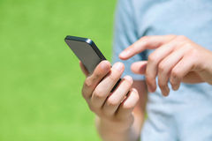 Boy holding a phone and a touch screen for finger against a gree Royalty Free Stock Image