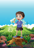 A boy holding a picture standing above a stump Royalty Free Stock Image