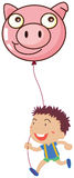 A boy holding a pig balloon Royalty Free Stock Image